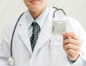 Doctor holding condom